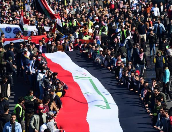 Estudantes universitários carregam a bandeira nacional iraquiana durante protesto em Bagdá
